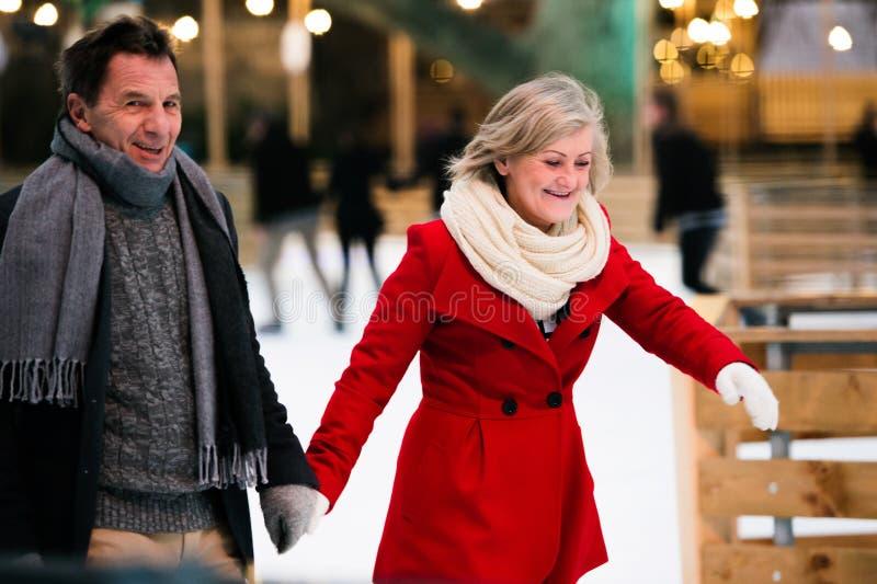 Mooi hoger paarijs die in stadscentrum schaatsen De winter stock fotografie