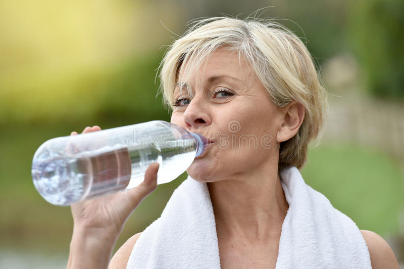 Mooi hoger vrouwen drinkwater na het excercising stock fotografie