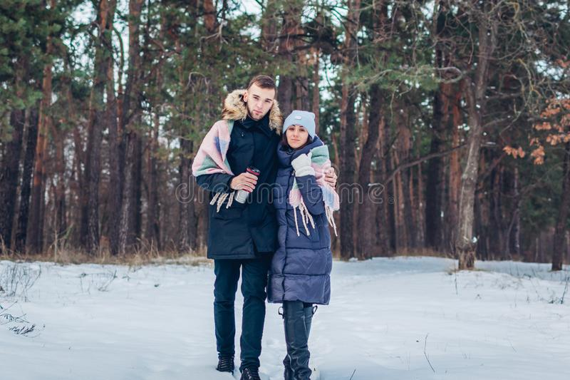 Mooi houdend van paar die in de winterbos samen lopen Mensen die pret hebben in openlucht stock foto