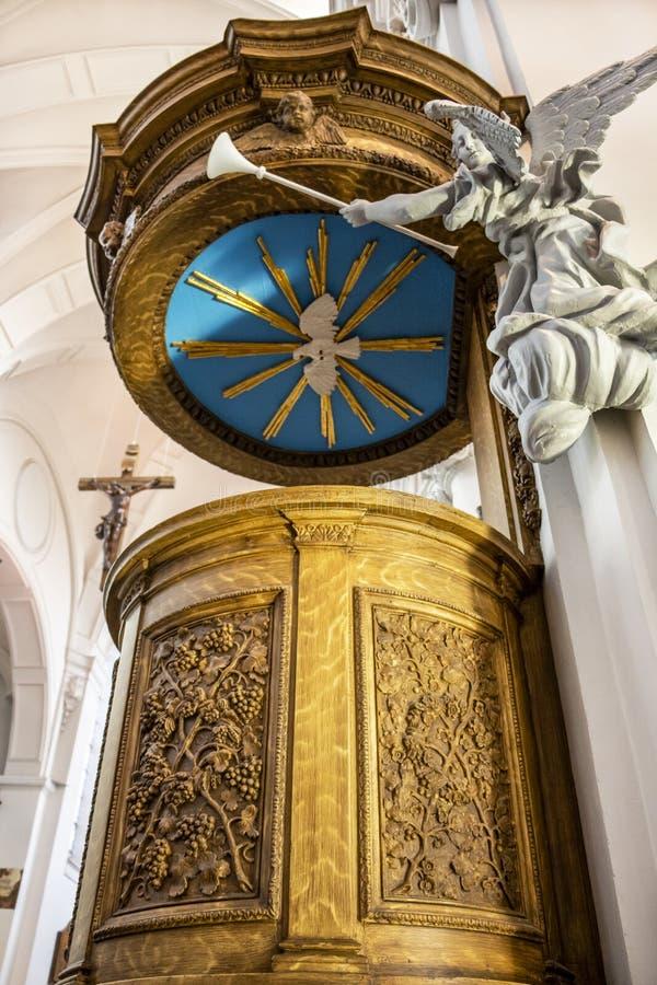 Mooi houten preekstoel en standbeeld van een engel met trompet in de Collegiale Kerk van St Bartholomew in Luik, België stock afbeeldingen