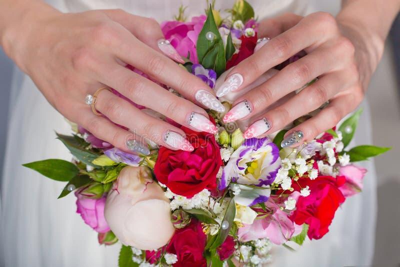 Mooi huwelijks bruids boeket van rozen en pioen met haar handen op het boeket, lange acrylspijkers met bergkristallen voor br stock foto