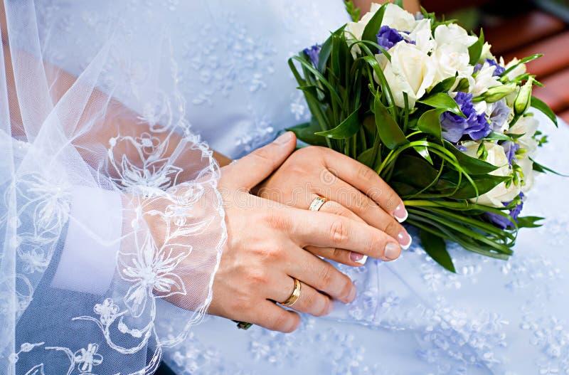 Mooi huwelijksboeket in bruiden en bruidegomshanden stock afbeeldingen