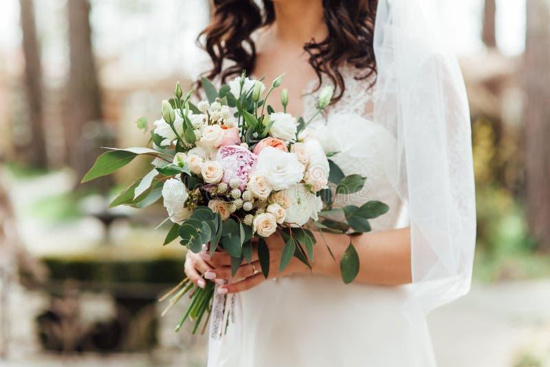 Mooi huwelijksboeket in handen van de bruid stock afbeelding