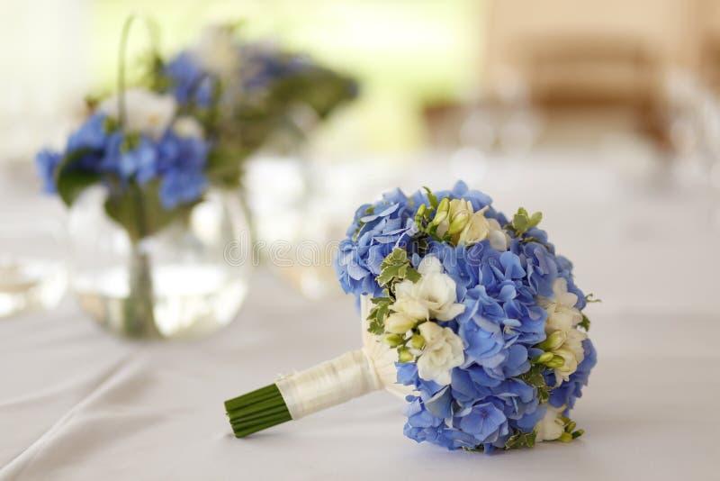 Mooi huwelijksboeket met witte en blauwe bloemen op lijst royalty-vrije stock foto