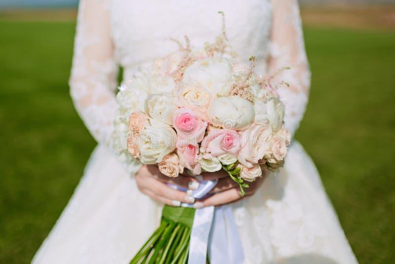 Mooi huwelijksboeket van bloemen in handen van de bruid stock foto