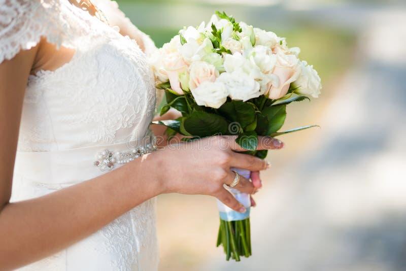 Mooi huwelijksboeket van bloemen in handen van jonge bruid royalty-vrije stock fotografie