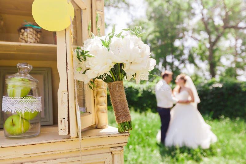Mooi huwelijksboeket van witte pioenen op de achtergrond van de bruid en de bruidegom stock afbeeldingen