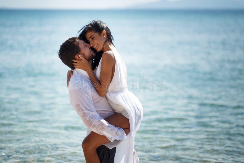 Mooi huwelijkspaar die en in turkoois water, Middellandse Zee in Griekenland kussen omhelzen stock afbeelding