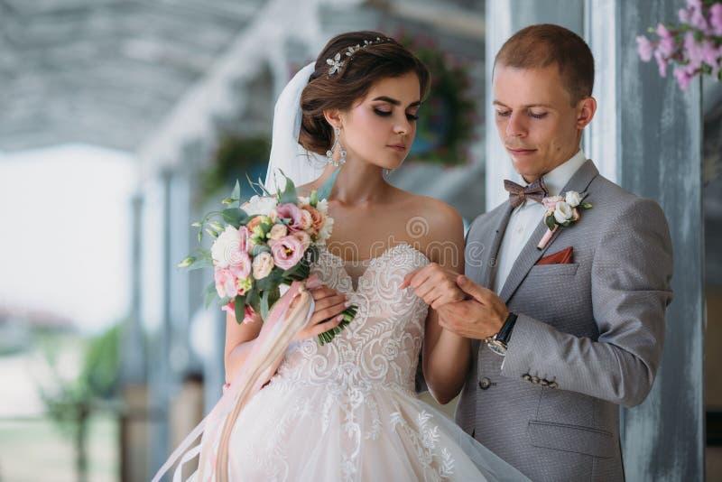 Mooi huwelijkspaar die in park met groene bomen op achtergrond koesteren Bruidegom in een bedrijfs grijs kostuum, wit overhemd in stock afbeelding