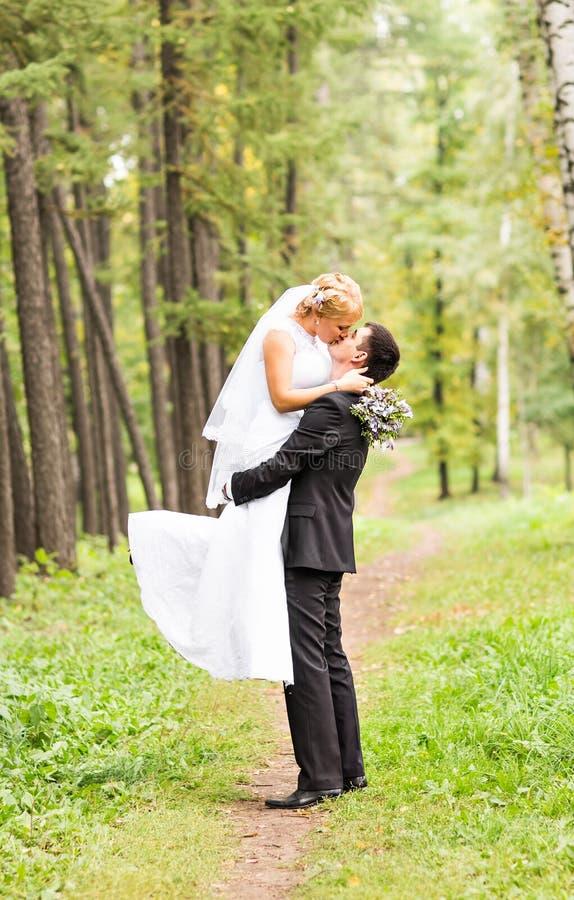Mooi huwelijkspaar in park Zij kussen en koesteren elkaar stock foto's