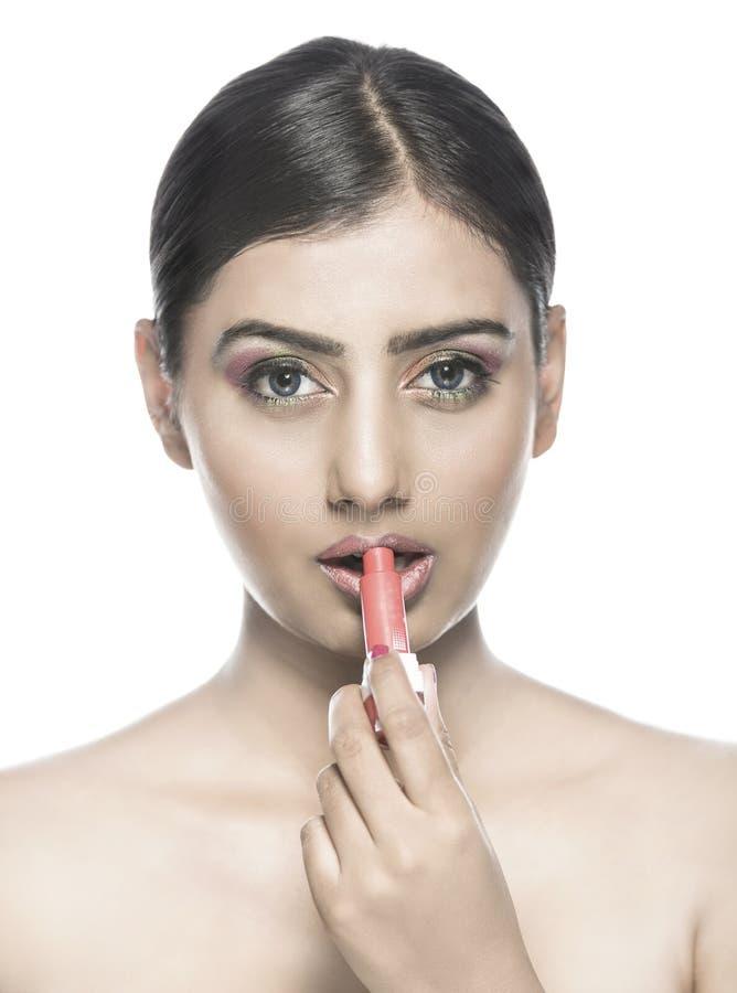 Mooi Indisch meisje die lippenstift of lipcolor toepassen stock foto
