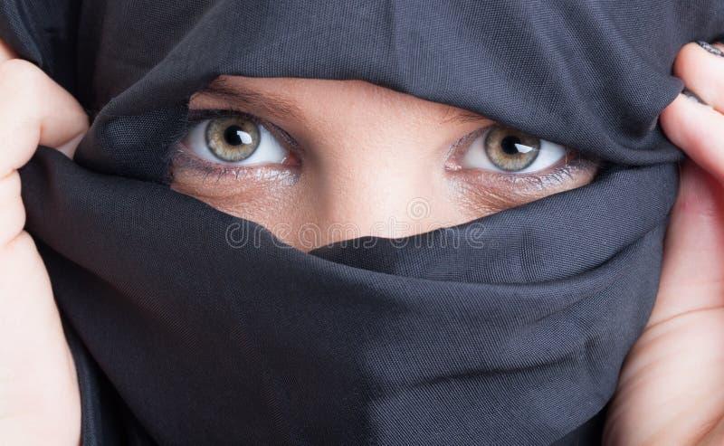 Mooi Islamitisch die vrouwenogen en gezicht door burka worden behandeld stock foto
