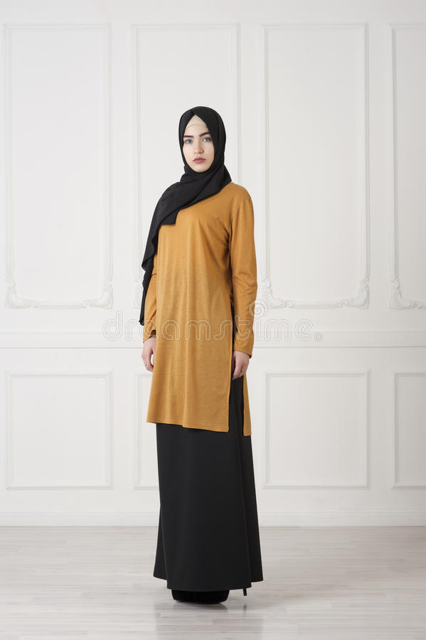 Mooi Islamitisch meisje in een gesloten, traditionele Moslimkleding, een studiofoto in de volledige groei royalty-vrije stock afbeeldingen