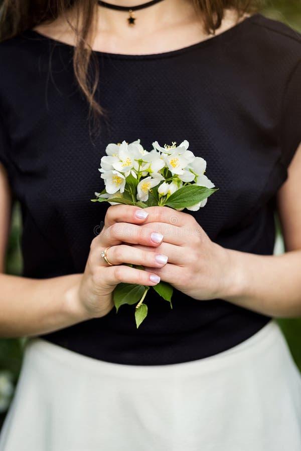 Mooi jasmijnboeket in meisjeshanden, Hand van jongelui die a houden stock afbeelding