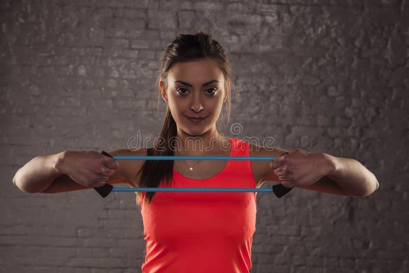 Mooi jong atletisch meisje die met elastisch rubber, st uitoefenen royalty-vrije stock foto