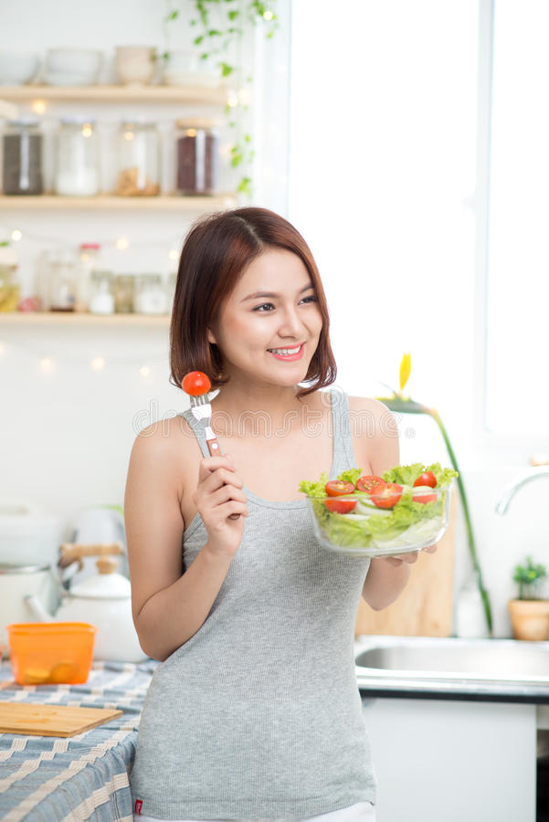 Mooi jong Aziatisch meisje die salade eten het glimlachen gelukkige meisjeseati stock afbeelding