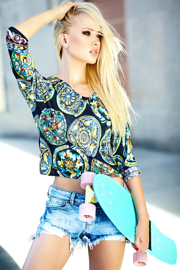 Mooi jong blond modelmeisje in de zomer hipster kleren met skateboard royalty-vrije stock afbeeldingen
