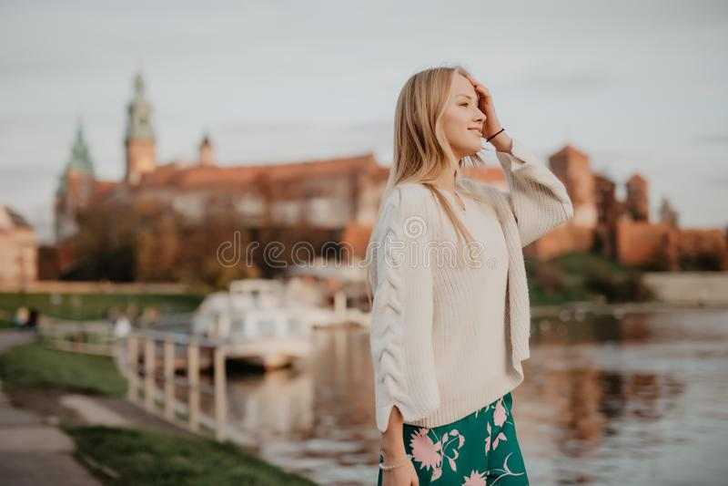 Mooi jong blonde die langs de dijk dichtbij rivier lopen en bij zonsondergang in de zomer stellen stock foto's