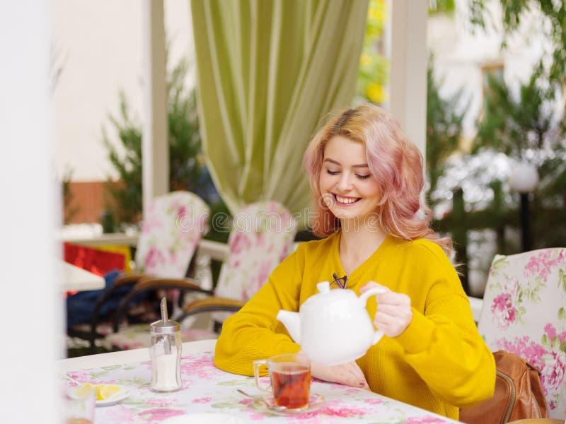 Mooi jong blonde in een gele sweater bij een lijst in een koffie stock fotografie