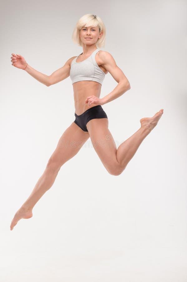 Mooi jong blonde in een sprong stock foto