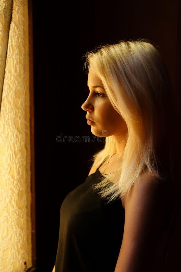 Mooi jong blonde meisje Dramatisch portret van een vrouw in dark Het dromerige wijfje kijkt in schemering Vrouwelijk silhouet royalty-vrije stock foto