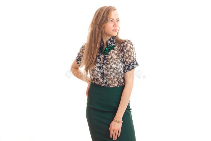 Mooi jong blondemeisje in blouse en rok het stellen op camera door het hoofd naar los te schroeven stock foto