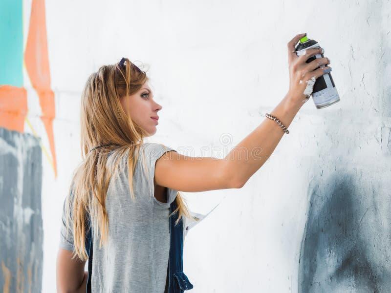 Mooi Jong Blondemeisje die graffiti van groot oog met aërosolnevel maken op stedelijke straatmuur Creatief art begaafd royalty-vrije stock afbeelding