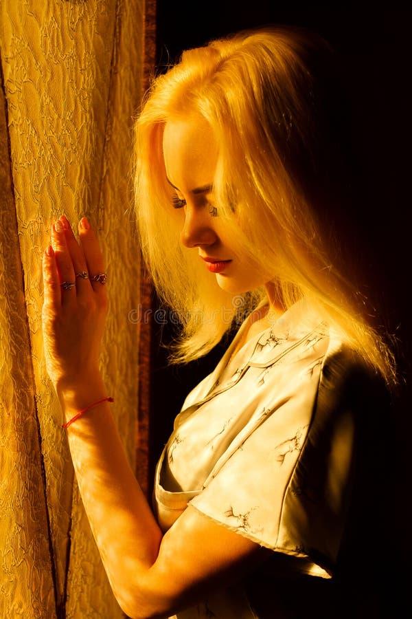 Mooi jong blondemeisje met een mooi gezicht en mooie ogen Dramatisch portret van een vrouw in dark Het dromerige wijfje kijkt stock foto