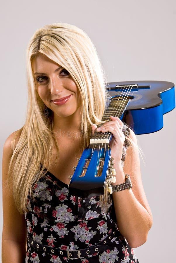 Mooi jong blondewijfje die een blauwe gitaar houden stock foto's