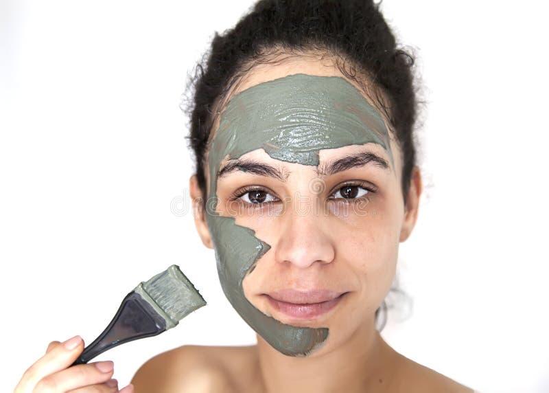 Mooi jong Braziliaans model met groen klei gezichtsmasker stock foto's