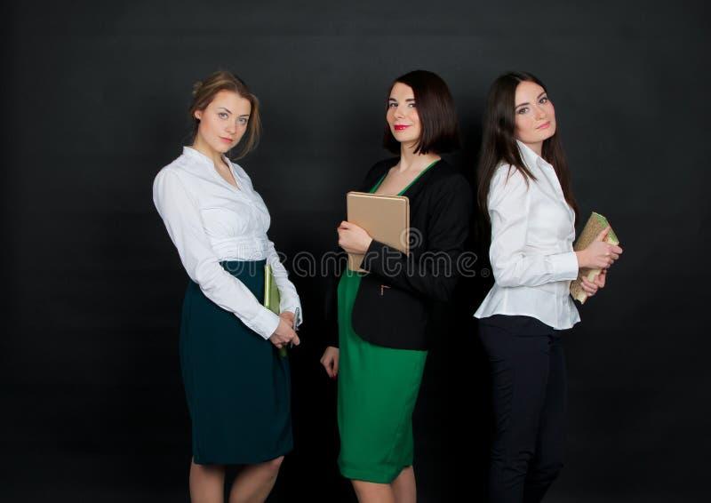 Mooi jong donkerbruin meisje drie die zich in witte blouse bevinden stock foto