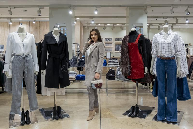 Mooi jong donkerbruin meisje in een kledingsopslag naast ledenpoppen zonder hoofd Het concept het winkelen en manier stock foto