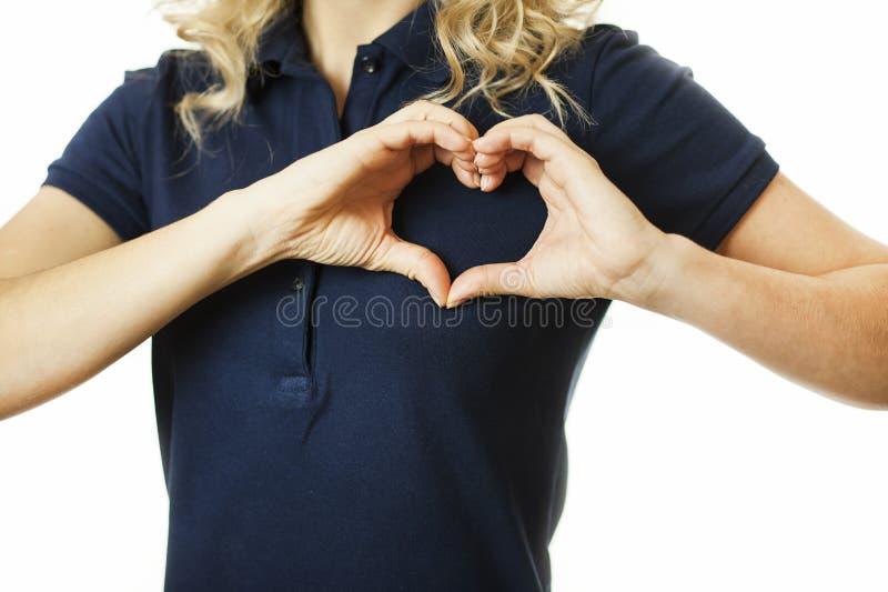 Mooi jong emotioneel meisje die hart van handen op een geïsoleerde achtergrond tonen Het concept liefde en gezondheid royalty-vrije stock afbeeldingen