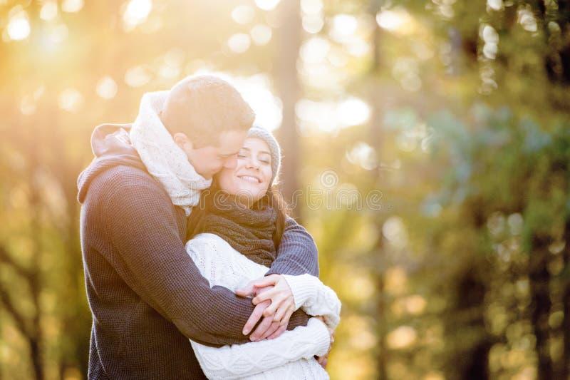 Mooi jong en paar die koesteren kussen Zonnige de herfstaard royalty-vrije stock afbeeldingen