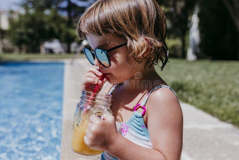 mooi jong geitjemeisje bij de pool die gezond jus d'orange in openlucht drinken en pret hebben Zomer en levensstijlconcept stock foto's