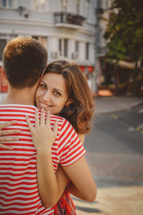 Mooi jong glimlachend paar in liefde koesteren, die in openlucht bij groene stadsstraat zitten, zomer De man leunt en vrouw i ach royalty-vrije stock fotografie