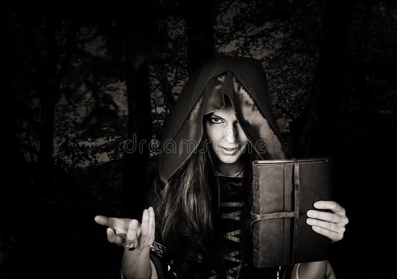 Mooi jong Halloween-heksen oud magisch boek royalty-vrije stock afbeeldingen