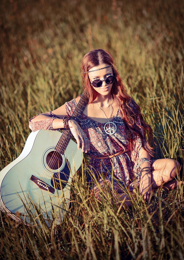 Mooi jong hippiemeisje met gitaarzitting op gras stock afbeelding