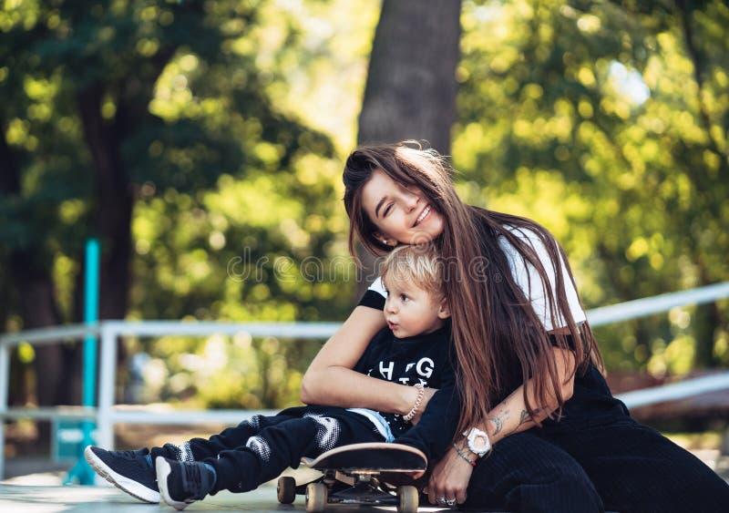 Mooi jong hipstermamma en weinig zoon bij skatepark royalty-vrije stock fotografie