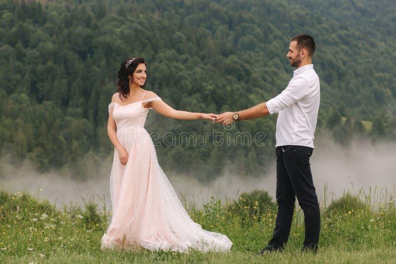 Mooi jong huwelijkspaar die zich op de groene helling, heuvel bevinden Bruidegom en bruid in Karpatische bergen stock foto