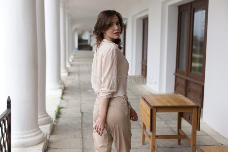 Mooi jong Kaukasisch glimlachend meisje met verleidelijke rode lippenstift die zich op veranda met witte pillarss op achtergrond  royalty-vrije stock afbeeldingen