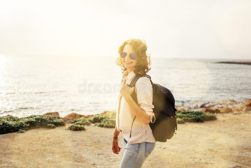 Mooi jong krullend modieus meisje in jeans en een roze overhemd en stock afbeeldingen