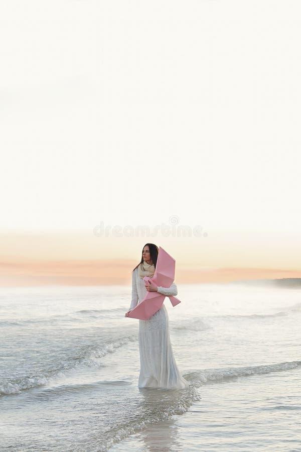 Mooi jong meisje alleen bij het overzees met roze vogel op zonsondergang stock foto
