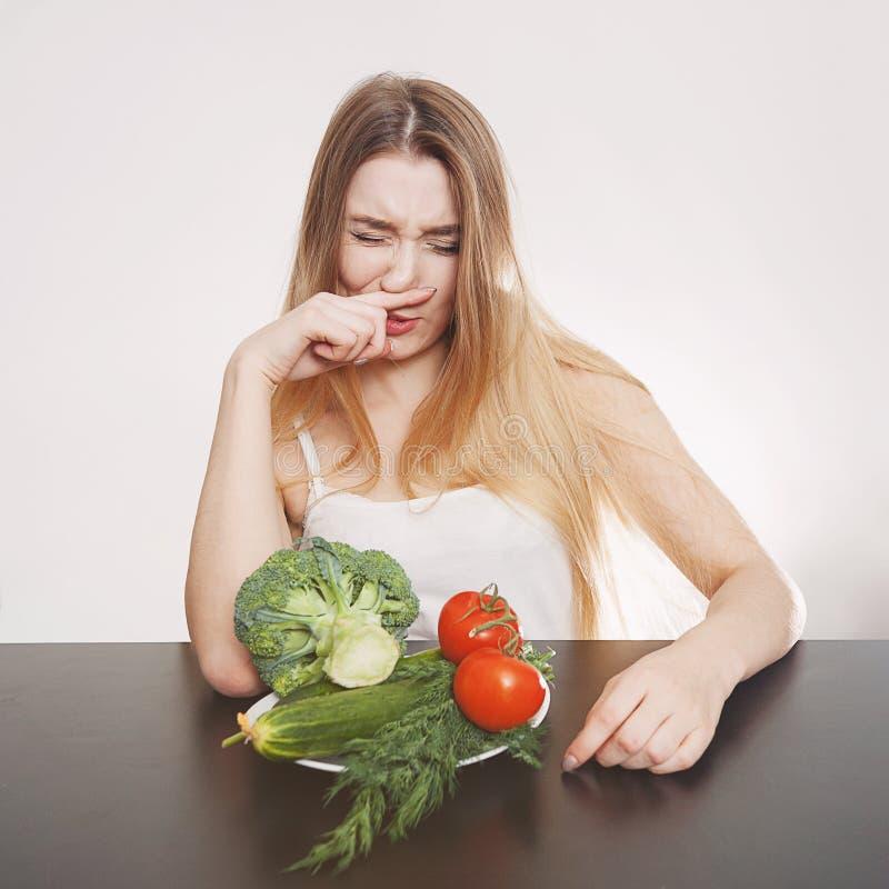 Mooi jong meisje bij een lijst met groenten voor salade Kok thuis Concept gezond, vegetarisch voedsel stock afbeeldingen