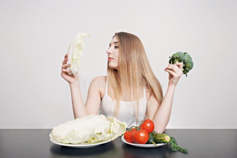 Mooi jong meisje bij een lijst met groenten voor salade Kok thuis Concept gezond, vegetarisch voedsel royalty-vrije stock foto