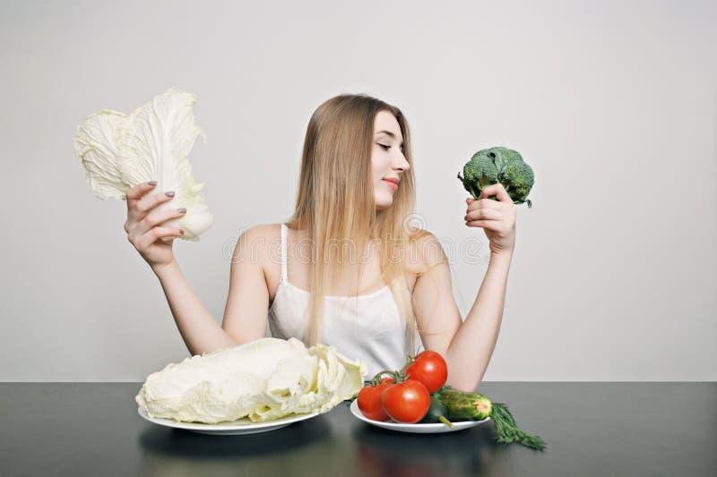 Mooi jong meisje bij een lijst met groenten voor salade Kok thuis Concept gezond, vegetarisch voedsel stock fotografie