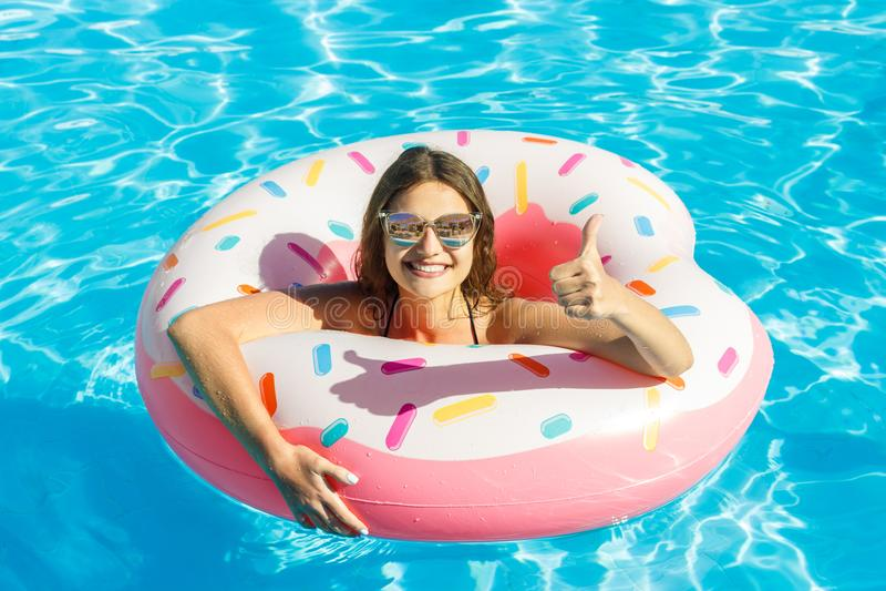 Mooi jong meisje in bikini met doughnut opblaasbare roze cirkel in blauw zwembad stock afbeelding