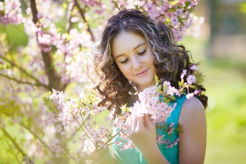 Mooi jong meisje in bloemen stock foto's