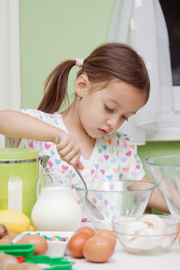 Mooi jong Meisje dat in het baksel van de Keuken werkt stock foto's