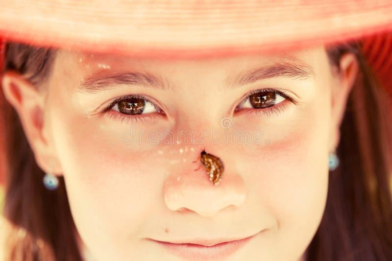 Mooi jong meisje in de zomerhoed met vlinder op neuscloseu royalty-vrije stock afbeelding